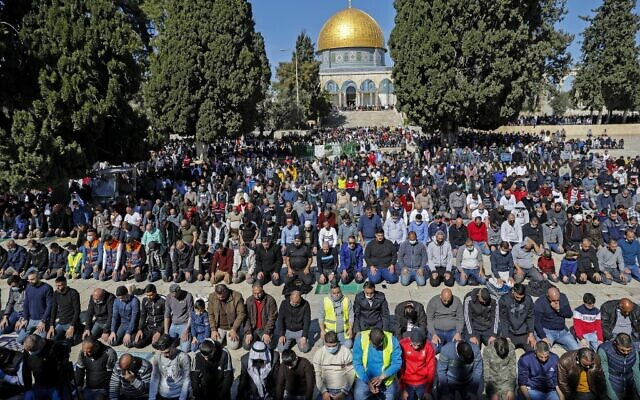 Des musulmans palestiniens prient devant le dôme du Rocher, sur le mont du Temple, près de la mosquée Al-Aqsa, le 12 février 2021. (Crédit :  AHMAD GHARABLI / AFP)