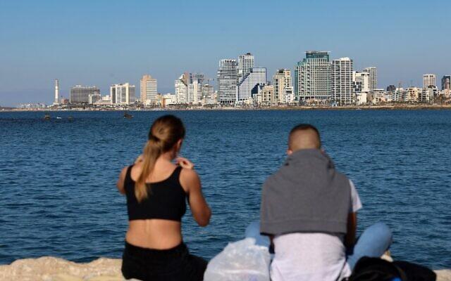 Un jeune couple devant la skyline de Tel Aviv, le 15 février 2021. (Crédit : Emmanuel DUNAND / AFP)