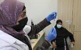 Une infirmière prépare une dose de vaccin Pfizer-BioNtech contre la COVID-19 dans un dispensaire de la principale ville bédouine du Negev, Rahat, le 17 février 2021. (Crédit :  HAZEM BADER / AFP)