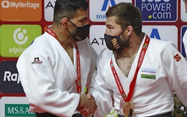 Le judoka de Mongolie d'origine iranienne Saeid Mollaei (à gauche), qui porte la médaille d'argent, salue le médaillé d'or ouzbek Sharofiddin Boltaboev après la finale de la catégorie masculine des moins de 81 kg du Grand Chelem 2021 de Tel Aviv, le 19 février 2021. (JACK GUEZ / AFP)