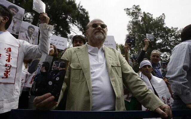 Anis Naccache, un militant libanais connu pour son rôle dans la prise d'otages de l'OPEP à Vienne en 1975 et la tentative d'assassinat près de Paris de l'ancien premier ministre iranien, tenant une photo de Georges Ibrahim Abdallah lors d'une manifestation devant l'ambassade de France dans la capitale Beyrouth, le 30 avril 2010. (Crédit : Anwar AMRO / AFP)