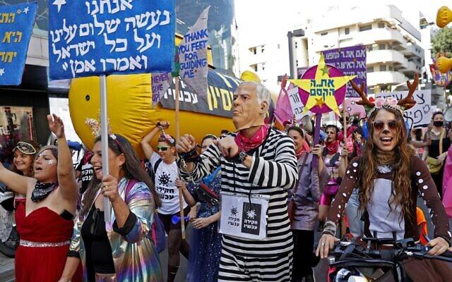 Des Israéliens déguisés prennent part à une parade pendant les fêtes juives de Pourim tout en manifestant contre le Premier ministre Benjamin Netanyahu, le 26 février 2021. (Crédit : JACK GUEZ / AFP)