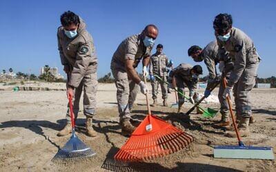Des bénévoles nettoient une plage polluée par le goudron dans la réserve naturelle de Tyre, dans le sud du Liban, suite à une pollution au goudron, le 27 février 2021. (Crédit :  Mahmoud ZAYYAT / AFP)