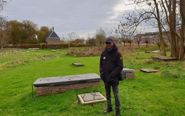 Sergio Berrenstein à côté de la tombe d'Elieser et de celle de son maître à l'entrée du cimetière juif d'Ouderkerk aan de Amstel, aux Pays-Bas, le 20 novembre 2020. (Autorisation : Cnaan Liphshiz/ JTA)