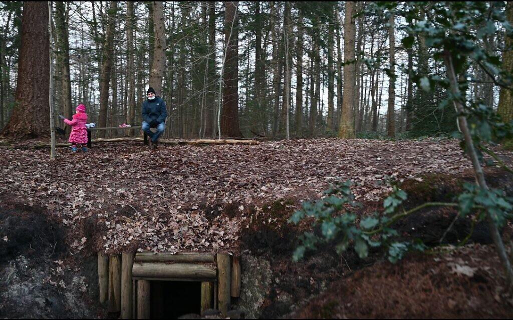 Une petite fille néerlandaise jour en compagnie de son grand-père au-dessus d'une reconstruction d'abri qui accueillait les Juifs vivant dans la clandestinité à Nieuwlande, aux Pays-Bas, le 25 janvier 2021. Crédit : Cnaan Liphshiz/ JTA)