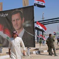 Un homme passe devant une affiche présentant le président syrien Bashar el-Assad en franchissant la frontière, au point de passage situé entre la ville de Qaim (Irak) et Boukamal (Syrie), le 30 septembre 2019. (Crédit : AP Photo/Hadi Mizban, File)