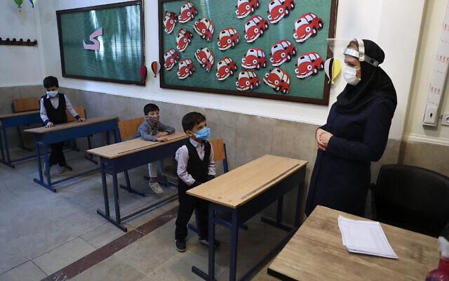Des élèves et leur professeur dans une classe après la cérémonie d'ouverture de l'école Hashtroudi à Téhéran, en Iran, le 5 septembre 2020. (AP Photo / Vahid Salemi)
