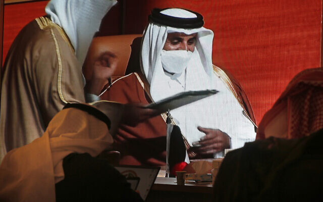 Des journalistes saoudiens devant un grand écran dans un centre de presse, montrant l'émir du Qatar, Sheikh Tamim bin Hamad Al Thani, au centre, lors de la 41e réunion du Conseil de coopération du Golfe (CCG), à Al Ula, en Arabie saoudite, le 5 janvier 2021. (AP Photo / Amr Nabil)