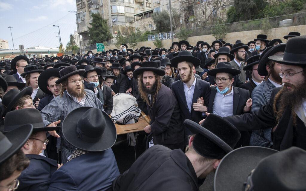 Des juifs ultra-orthodoxes portent le corps du rabbin Meshulam Soloveitchik lors de ses funérailles à Jérusalem, le dimanche 31 janvier 2021. La cérémonie de masse s'est déroulée en dépit de la réglementation sanitaire du pays qui interdit les grands rassemblements publics, pendant un confinement national visant à freiner la propagation du virus. (AP Photo/Ariel Schalit)