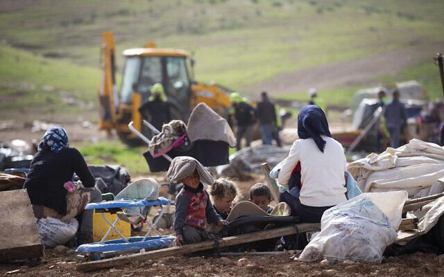 Des Bédouins palestiniens regardent les troupes israéliennes démolir des tentes et d'autres structures du village de Khirbet Humsa dans la vallée du Jourdain, en Cisjordanie, le 3 février 2021. (AP Photo / Majdi Mohammed)