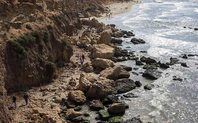 Des Israéliens nettoient du goudron provenant d'une fuite de pétrole dans la mer méditerranée dans la réserve naturelle de Gador, près de Hadera, le 20 février 2021. (Crédit : AP Photo/Ariel Schalit)