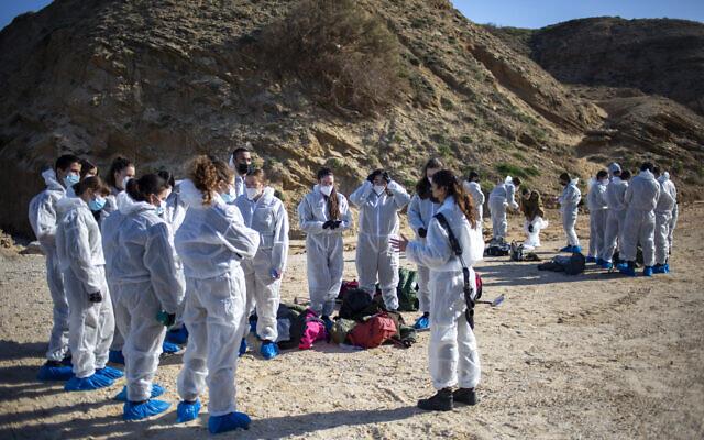Des soldats israéliens portant des habits de protection écoutent les conseils qui leur sont donnés avant les opérations de nettoyage du goudron qui s'est accumulé sur une plage après une fuite de pétrole en méditerranée sur la plage de la réserve naturelle de Sharon, près de Gaash, le 22 février 2021. (Crédit : AP Photo/Ariel Schalit)