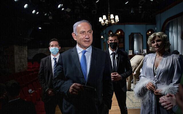 Le Premier ministre Benjamin Netanyahu rencontre l'actrice Carmit Mesilati Kaplan, à droite, lors d'une visite au théâtre Khan avant la réouverture du secteur culturel, à Jérusalem, le 23 février 2021. (Crédit : Ohad Zwigenberg / Pool Photo via AP)