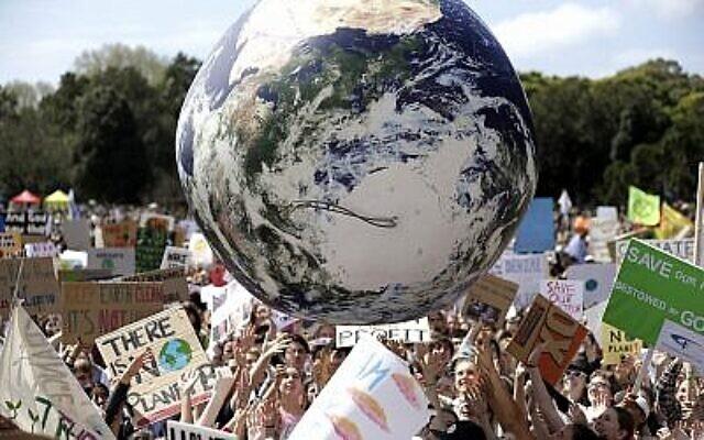 Un grand globe gonflable est projeté dans la foule alors que des milliers de manifestants, dont beaucoup d'écoliers, se rassemblent à Sydney, le 20 septembre 2019, pour appeler à l'action afin de se prémunir contre le changement climatique. (AP Photo/Rick Rycroft)