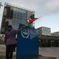 Une manifestante pose avec un drapeau palestinien devant la Cour pénale internationale, CPI, lors d'un rassemblement exhortant la Cour à poursuivre l'armée israélienne pour crimes de guerre, à La Haye, Pays-Bas, le 29 novembre 2019. (AP/Peter Dejong)