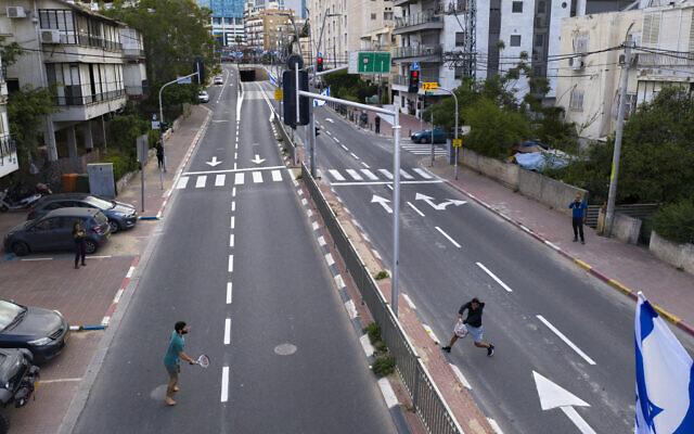 Des Israéliens jouent au tennis sur une route vide pendant le confinement imposé par le gouvernement pour aider à réduire la propagation du coronavirus à Ramat Gan, près de Tel Aviv, le 9 avril 2020. (Crédit : AP Photo/Oded Balilty)
