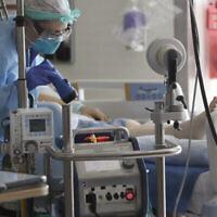 Photo d'illustration : Un infirmier surveille une machine ECMO (oxygénation par membrane extracorporelle) reliée à un malade à l'hôpital Harborview de Seattle, le 8 mai 2020. (Crédit : Elaine Thompson/AP)