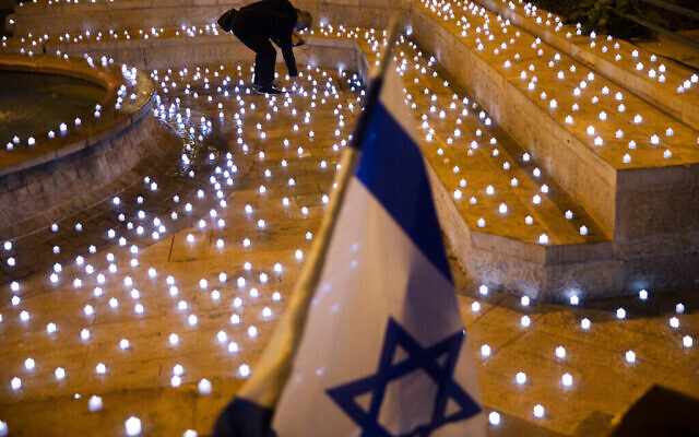 Un homme allume des bougies LED dans un mémorial pour les victimes israéliennes de la COVID-19, à Jérusalem, le dimanche 8 novembre 2020. (Crédit : AP Photo / Oded Balilty)