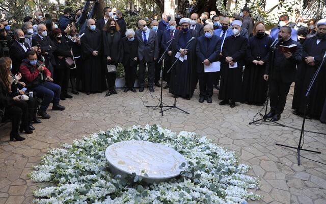 Des militants, des proches et des religieux se rassemblent et prient autour d'un monument dédié à Lokman Slim lors d'un hommage au militant libanais tué et critique vocal du groupe du Hezbollah, une semaine après avoir été retrouvé mort dans sa voiture avec plusieurs balles dans le corps, dans la banlieue sud de Beyrouth, au Liban, le jeudi 11 février 2021. (Crédit : AP / Hussein Malla)