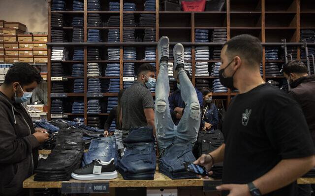 Des clients et des employés dans un magasin de vêtements d'un centre commercial à Beer Sheva, dans le sud d'Israël, le 21 février 2021. (Crédit : AP/Tsafrir Abayov)