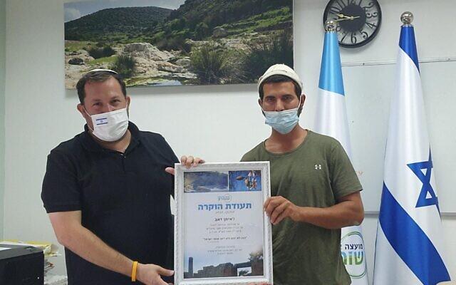 Eitan Zeev, (à droite), reçoit un prix du chef du Conseil régional de Samarie, Yossi Dagan, le 2 septembre 2020, pour son implication dans un affrontement avec des Palestiniens au sujet d'un morceau de terre agricole cet été-là. (Roi Hadi)