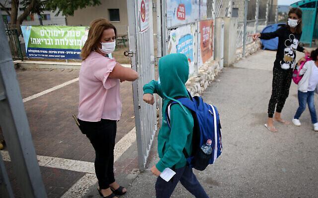 Des enfants portant des masques faciaux se rendent à l'école à Safed, le premier jour de la rentrée des classes, le 1er novembre 2020. (Crédit : David Cohen/Flash90)