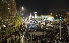Des juifs ultra-orthodoxes affrontent la police à l'entrée de Jérusalem alors qu'ils protestent contre l'arrestation d'un étudiant de yeshiva qui voulait échapper au service militaire, le 22 décembre 2020. (Yonatan Sindel/Flash90)