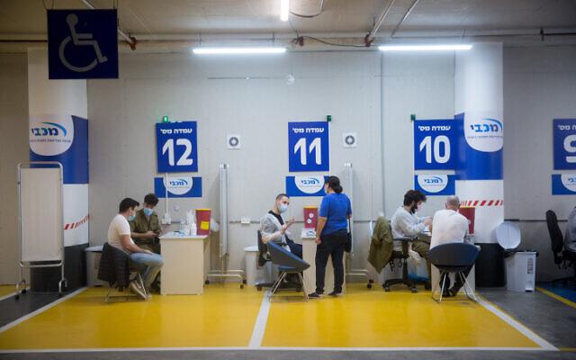 Des Israéliens se font vacciner contre le COVID-19 dans un centre de vaccination de Maccabi Health au centre commercial de Givatayim, près de Tel Aviv, le 4 février 2021. (Miriam Alster/Flash90)