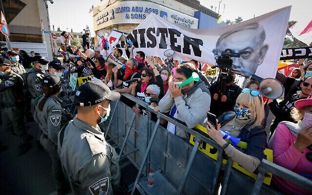 Des manifestants anti-Netanyahu devant le tribunal de district de Jérusalem, alors que le Premier ministre Benjamin Netanyahu arrive pour son procès au tribunal de district, le 08 février 2021. (Crédit: Olivier Fitoussi/Flash90)
