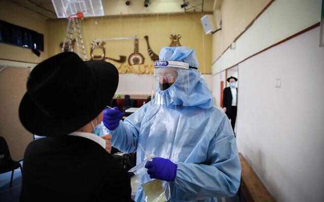 Un personnel soignant fait un test au coronavirus sur un ultra-orthodoxe à Safed, le 10 février 2021. (Crédit : David Cohen/Flash90)