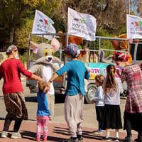 Des Israéliens en costume dansent  avant la fête de Pourim à Efrat, à Gush Etzion, le 12 février 2021. (Crédit : Gershon Elinson/Flash90)