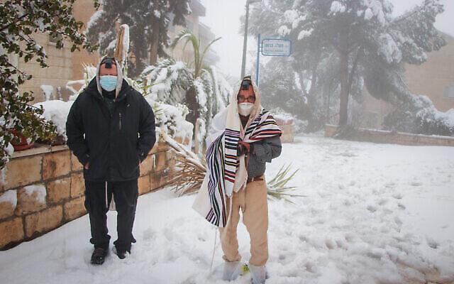 Des hommes en prière dehors dans la neige, dans l'implantation d'Efrat en Cisjordanie, le 18 février 2021. (Gershon Elinon / Flash 90)