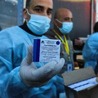 Illustration : Des Palestiniens du ministère de la Santé reçoivent une cargaison de doses de vaccin russe contre le coronavirus Spoutnik V envoyée par les Émirats arabes unis, après que les autorités égyptiennes ont autorisé l'entrée à Gaza par le point de passage de Rafah dans le sud de la bande de Gaza, le 21 février 2021. (Abed Rahim Khatib/Flash90)