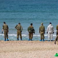 Des soldats israéliens nettoient le goudron sur la plage de Palmachim à la suite d'une marée noire en mer, qui a recouvert la plus grande partie du littoral israélien, le 22 février 2021. (Yonatan Sindel/Flash90 *** Local Caption)