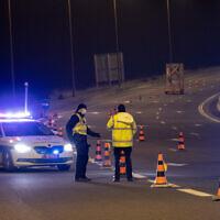 La police met au point un barrage routier temporaire sur la Route 1, près de Jérusalem, pendant un couvre-feu nocturne pour la fête de Pourim, le 25 février 2021. (Crédit : Yonatan Sindel/Flash90)