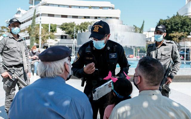 Des policiers israéliens font appliquer le règlement COVID-19 à Tel-Aviv, le 27 février 2021. (Tomer Neuberg/Flash90)