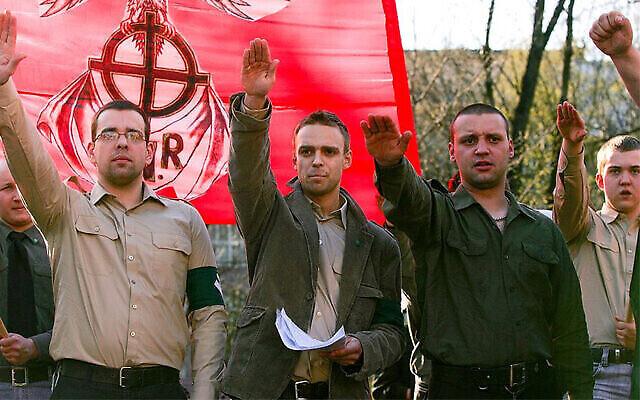 Tomasz Greniuch, au centre, a des papiers dans une main, et de l'autre, fait un geste qui semble être un salut nazi, lors d'un événement d'extrême droite en Pologne en 2007. (Bartosz Siedlik ; Autorisation de Gazeta Wyborcza via JTA)