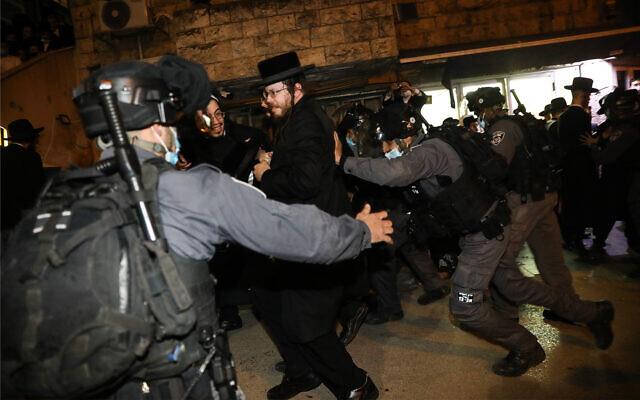 Des hommes ultra-orthodoxes affrontent la police lors d'une manifestation contre les restrictions sur le coronavirus à Jérusalem, le 9 février 2021. (Crédit : Noam Revkin Fenton/Flash90)