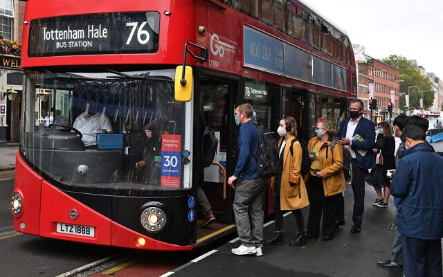 Photo d'illustration : Des londoniens montent à bord d'un bus aux abords de la gare de Waterloo, à Londres, le 23 septembre 2020. (Crédit : Dominic Lipinski/PA via AP)