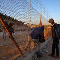 Des travailleurs palestiniens de Hébron, en Cisjordanie, avec leurs effets personnels, entrent sur le territoire israélien à travers un trou creusé dans la clôture de sécurité, aux abords de Hébron, le 31 janvier 2021. (Crédit : Wisam Hashlamoun/Flash90)