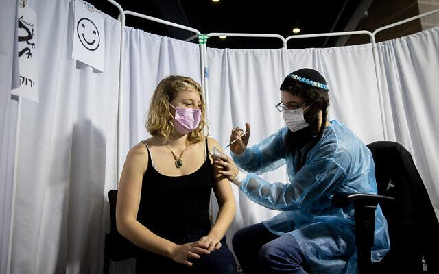 Une Israélienne se fait vacciner contre la COVID-19 à Jérusalem, le 10 février 2021. (Crédit : Yonatan Sindel / Flash90)
