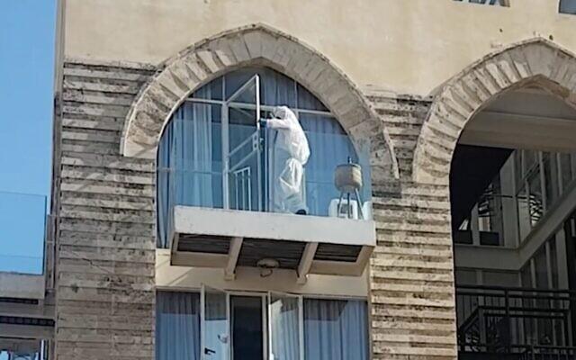Capture d'écran d'une vidéo d'un enquêteur recueillant des preuves médico-légales dans un hôtel de quarantaine à Jaffa dans le cadre d'une affaire de viol présumé. (Capture d'écran vidéo)