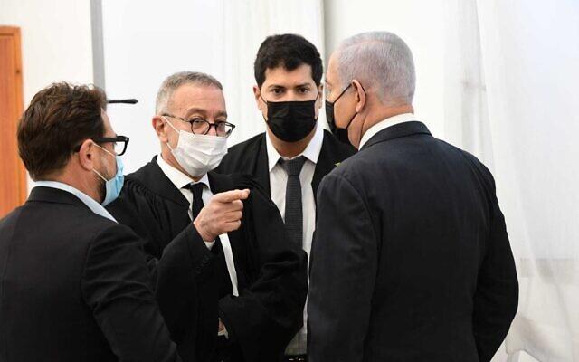 Le Premier ministre Benjamin Netanyahu (à droite) et ses avocats discutent dans la salle d'audience du tribunal de district de Jérusalem pour son procès pour corruption, le 8 février 2021. (Reuven Castro/Pool)