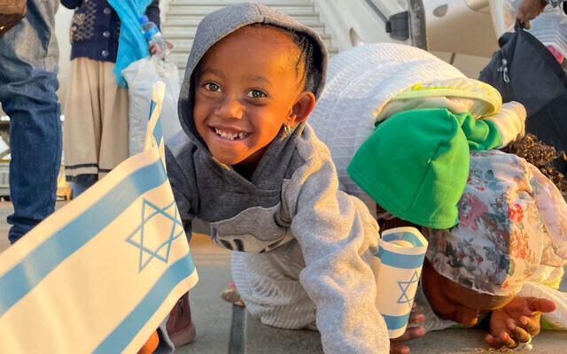 Une petite fille sourit en arrivant d'Éthiopie alors que sa mère embrasse le sol à l'aéroport Ben Gurion en Israël, le 12 février 2021. (Autorisation de l'ICEJ via JTA)
