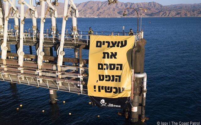 """Une manifestation contre l'expansion des activités au port pétrolier de l'entreprise EAPC à Eilat, avec une bannière disant : """"Arrêt immédiat de l'accord sur le pétrole,"""" le 10 février 2021. (Crédit : Egor Iggy Petrenko/Coast Patrol)"""