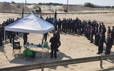Des policiers reçoivent des instructions à la plage de Nitzanim, dans le sud d'Israël, avant de rejoindre des bénévoles pour aider à nettoyer le goudron d'une marée noire, le 22 février 2021 (Crédit : Menachem Fried/Autorité de la Nature et des Parcs)