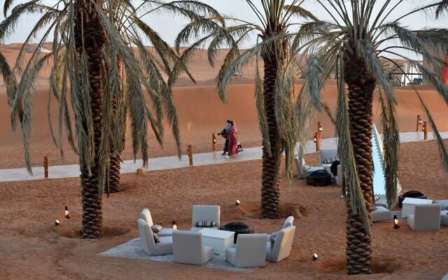 """Des visiteurs marchent sous des palmiers à l'""""Oasis de Riyad"""", une retraite de luxe dans le désert de Thumamah, à la périphérie de la capitale saoudienne, le 1er février 2021. (Crédit : FAYEZ NURELDINE / AFP)"""