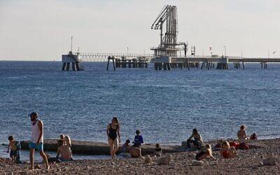 Des Israéliens sur une plage de la mer Morte, à proximité du Terminal pétrolier de l'EAPC (Eilat-Ashkelon Pipeline) dans la ville portuaire d'Eilat, dans le sud du pays, le 10 février 2021. (Crédit : Menahem Kahana / AFP)