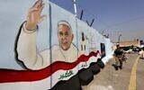 Un membre des forces irakiennes passe devant une peinture murale représentant le pape François saluant à côté d'un drapeau national irakien dessiné sur un mur anti-explosion devant l'église catholique syriaque de Notre-Dame de la Délivrance, dans le quartier de Karrada à Bagdad, la capitale irakienne, le 1er mars 2021, alors que les préparatifs de la visite du pontife sont en cours. (Crédit : Sabah ARAR / AFP)