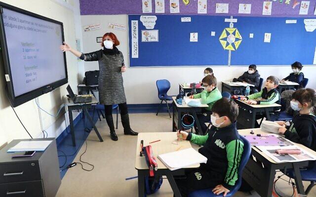 Les élèves portant des masques de protection écoutent une enseignante dans une classe d'Ankara, le 2 mars 2021. (Crédit : Adem ALTAN / AFP)